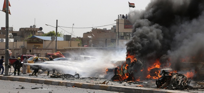 Iraqi firefighters try to extinguish burning vehicles moments after one in a series of bombs hit the Shiite stronghold of Sadr City, in Baghdad, Iraq, May 13, 2014.