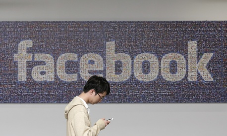 A man walks past a Facebook sign at the company's campus in Menlo Park, Calif., on June 11, 2014.