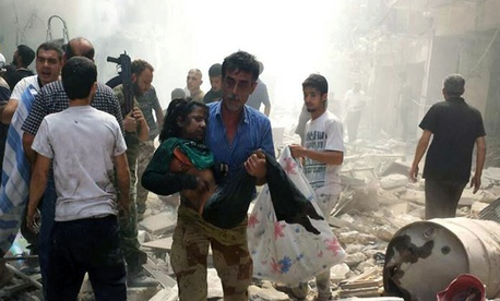 A man carries a wounded girl following a Syrian government airstrike at the Karm al-Jabal area of Aleppo, on June 26, 2014.