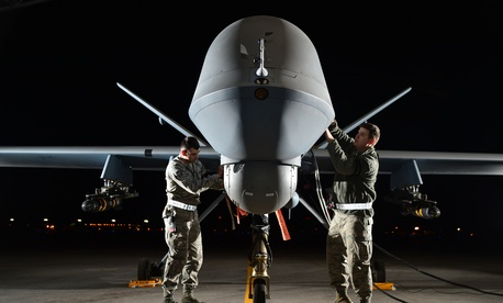 Two airmen prepare an MQ-9 Reaper for flight during exercise Combat Hammer, on May 15, 2014.