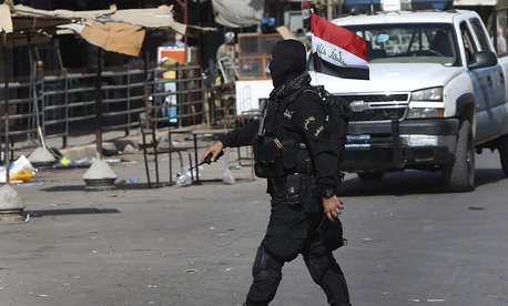A masked Iraqi Shiite militiamen cross a street during a parade in the oil-rich province of Kirkuk, on June 21, 2014.