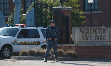 Navy security stands watch at the Washington Navy Yard, Sept. 19, 2013. The Washington Navy Yard began returning to nearly normal operations three days after it was the scene of a mass shooting in which a gunman killed 12 people.
