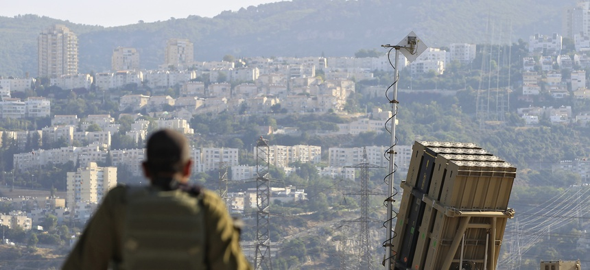 An Israeli soldier sits next to an Iron Dome rocket interceptor deployed near Haifa, on August 28, 2013.
