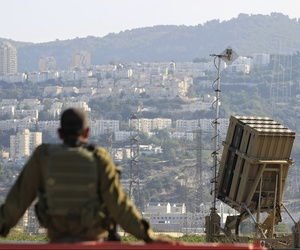 An Israeli soldier sits next to an Iron Dome rocket interceptor deployed near Haifa, on August 28, 2013.