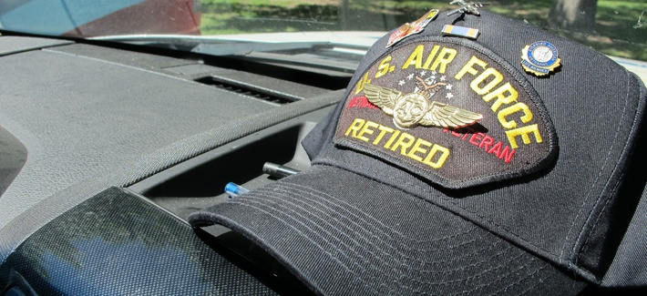 A Vietnam War veteran's cap sits on the dashboard of a vehicle used to transport veterans to medical appointments in New Mexico.