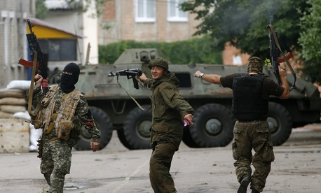 Pro-Russian fighters in the city of Donetsk dance and fire their weapons in the air in a Ukrainian military unit recently captured by their forces, on June 27, 2014.
