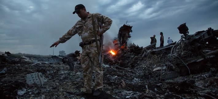People walk amongst the debris at the crash site of a passenger plane near the village of Hrabove, Ukraine, July 17, 2014.