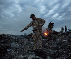 People walk amongst the debris at the crash site of a passenger plane near the village of Hrabove, Ukraine, July 17, 2014.