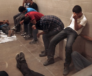 Immigrants sit at the McAllen Border Patrol Station in McAllen, Texas, while being detained, on July 15, 2014.