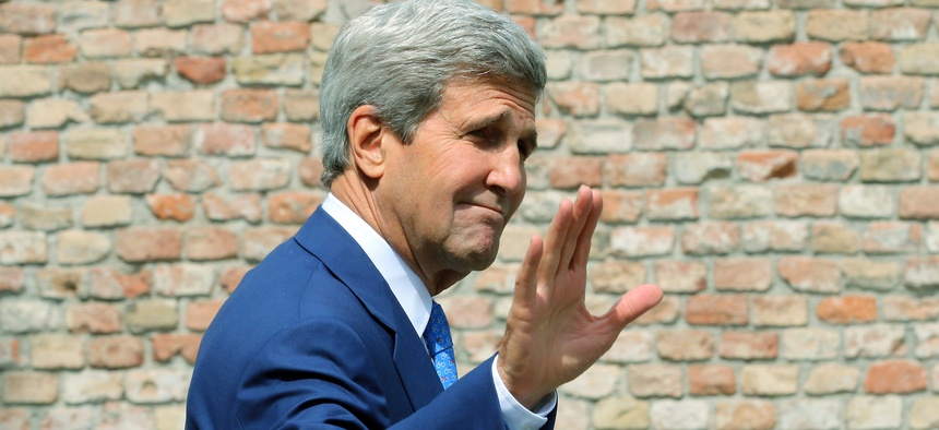 U.S. Secretary of State John Kerry waves as he arrives in front of a hotel where closed-door nuclear talks on Iran take place in Vienna, Austria, July 14, 2014.