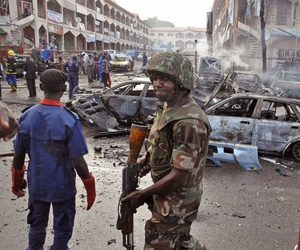 A Nigerian soldier walks at the scene of a car bomb explosion in Abuja, Nigeria, on June 25, 2014.
