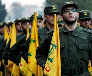 In this November 12, 2010 file photo, Hezbollah fighters hold their party flags, as they parade during the opening of new cemetery for colleagues who died in fighting against Israel, in a southern suburb of Beirut, Lebanon.