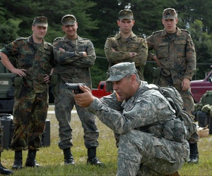 A sergeant with the 200th Military Police Command trains German soldiers during a 9mm marksmanship training course.