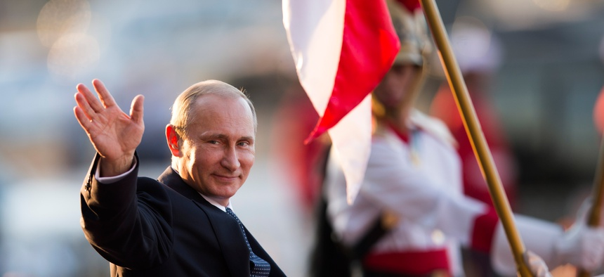 Russia's President Vladimir Putin waves to photographers as he leaves the Itamaraty Palace after the BRICS Summit in Brasilia, Brazil, July 16, 2014.