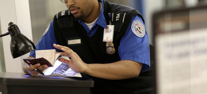 A TSA official checks a passport at a checkpoint at Baltimore-Washington International Airport in Linthicum, Md.
