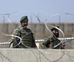 Afghan National Army soldiers stand guard at the gate of Camp Qargha, where a man opened fire on coalition and Afghan troops on Tuesday.