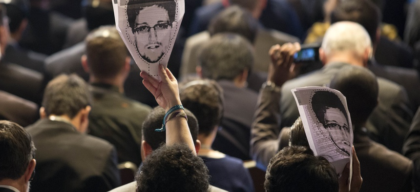 Participants at an internet conference in Sao Paolo hold up pictures of Edward Snowden during a session.