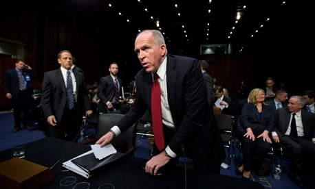 CIA Director John Brennan gathers his documents after testifying before the Senate Intelligence Community for his nomination hearing, on February 7, 2013.