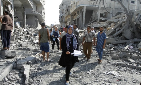 A human rights worker walks through a devastated area in Gaza City, on August 2, 2014.