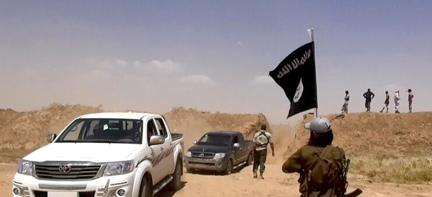 ISIL insurgents wave flags as they cross the border between Syria and Iraq.
