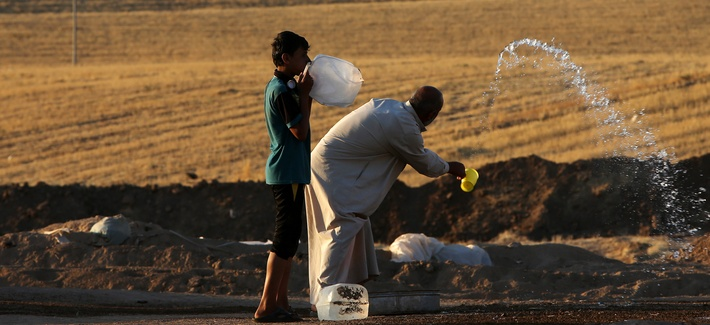 Iraqi refugees spray water outside of Erbil in northern Iraq, on June 22, 2014.