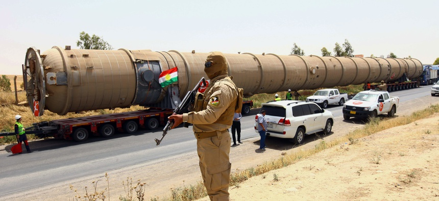 A Kurdish Peshmerga fighter stands guard as new equipment arrives at Kalak refinery on the outskirts of Irbil, Iraq, Monday, July 14, 2014, as Kurdish authorities are trying to help ease the fuel shortage.
