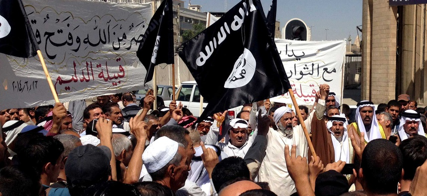 Demonstrators in Mosul chant pro-ISIL cheers in front of the provincial government headquarters, on June 16, 2014.
