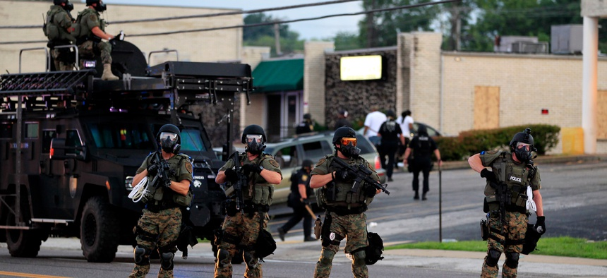 Police wearing riot gear try to disperse a crowd, Aug. 11, 2014, in Ferguson, Mo.