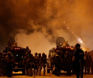 Police wait to advance after tear gas was used to disperse a crowd in Ferguson, Mo., on Sunday, Aug. 17, 2014.