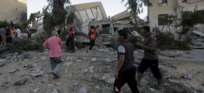 Palestinians and firefighters inspect the rubble of a five-storey building of the Sheikh Zaid housing project following an Israeli strike, on August 26, 2014.