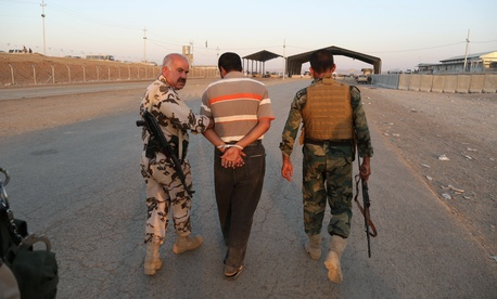 Kurdish Peshmerga fighters detain a man suspected as a militant for the ISIL.