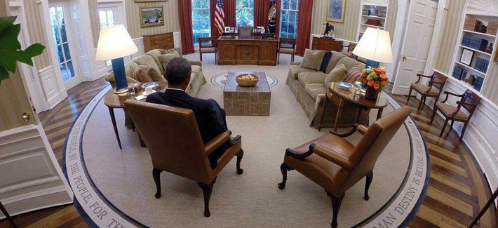 President Obama reads briefing material in the Oval Office, on August 29, 2014.