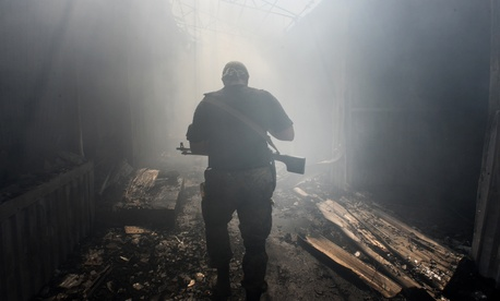A Pro-Russian rebel walks in a passage at the local market damaged by shelling in Petrovskiy district in the town of Donetsk, eastern Ukraine, Aug. 26, 2014.