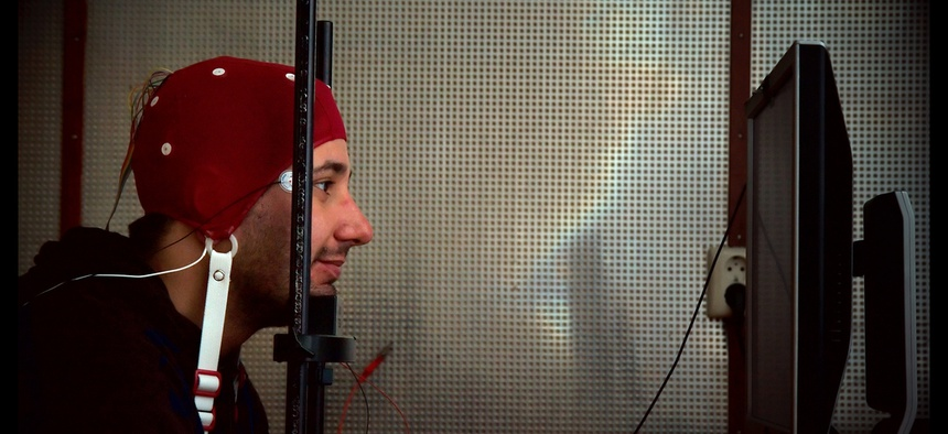 A man wears an EEG cap and stares into a computer screen as part of an experiment with brain-computer interfacing.