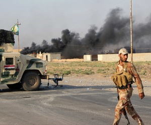 Iraqi security forces and a Shiite militiaman take part in an operation against the Islamic State outside of the northern town of Amerli.