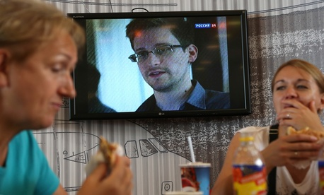In this June 26, 2013 file photo transit passengers eat at a cafe with a TV screen with a news program showing a report on Edward Snowden, in the background, at Sheremetyevo airport in Moscow, Russia.