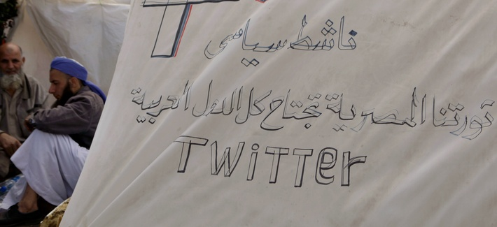 Protesters sit next to their tent, decorated with the logos of Facebook and Twitter in Tahrir Square in Cairo, Egypt, March 9, 2011.