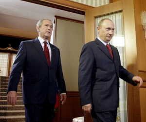 Former President George W. Bush walks with Russian President Vladimir Putin at the Bocharov Ruchei presidential residence in Sochi, on April 6, 2008.