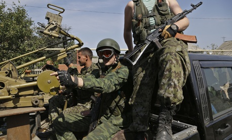 Pro-Russian fighters in Donetsk sit in a vehicle with a heavy machine gun attached, on September 7, 2014.