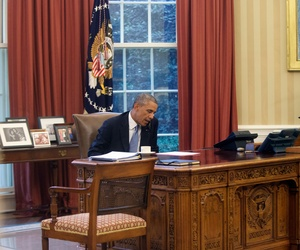 In this image made through a window of the Oval Office, President Barack Obama speaks on the phone to Saudi Arabia's King Abdullah from his desk at the White House in Washington, Sept. 10, 2014.