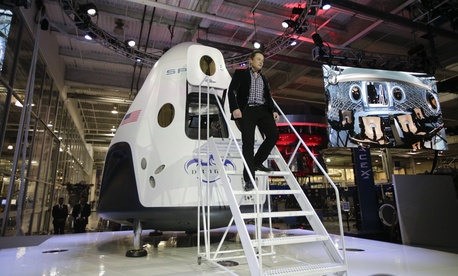 Elon Musk, CEO and CTO of SpaceX, walks down the steps as he introduces the SpaceX Dragon V2 spaceship at company headquarters in Hawthorne, Calif.