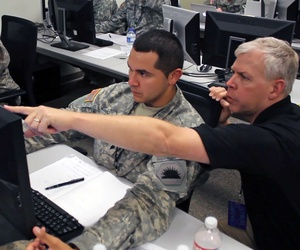 A network analyst with the California Army National Guard works with another analyst to defend against a virus attack during 2014 Cyber Shield exercise.