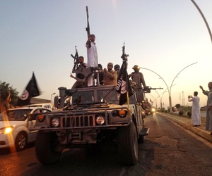 Fighters from the Islamic State group parade in a commandeered Iraqi security forces armored vehicle down a main road in Mosul, Iraq, on June 23.