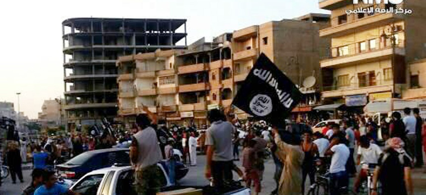 Fighters from the Islamic State hold flags and march in the northern Syrian city of Raqqa.