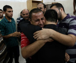 Palestinian relatives comfort each other after seeing the body of another relative at the Najar hospital in Gaza, on August 26, 2014.