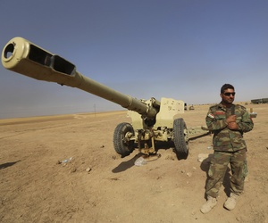 A Kurdish peshmerga fighter stands next to a firearm in Mahmoudiyah, Iraq, on October 1, 2014.