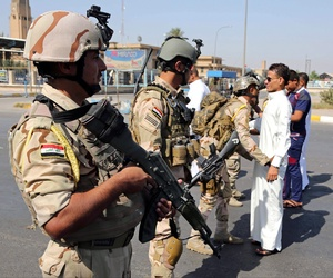 Iraqi Army soldiers search youths amid tight security during Eid al-Adha celebrations in Baghdad, Iraq, Oct. 6, 2014.