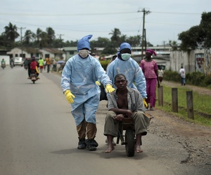 Residents of the St. Paul Bridget neighborhood take a man suspected of carrying the Ebola virus to a clinic, in Monrovia, Liberia.