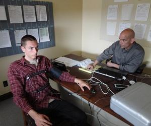 A photo of a man undertaking a polygraph test.