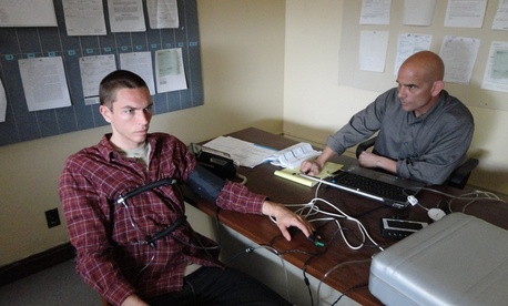 A photo of a man undertaking a polygraph test.